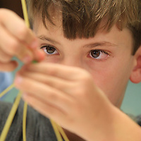 William Valentine, 8, of Guntown works on building a teepee out of spaghetti and gummy candy during an engineering day project at the Lee County Library Tuesday in Tupelo.