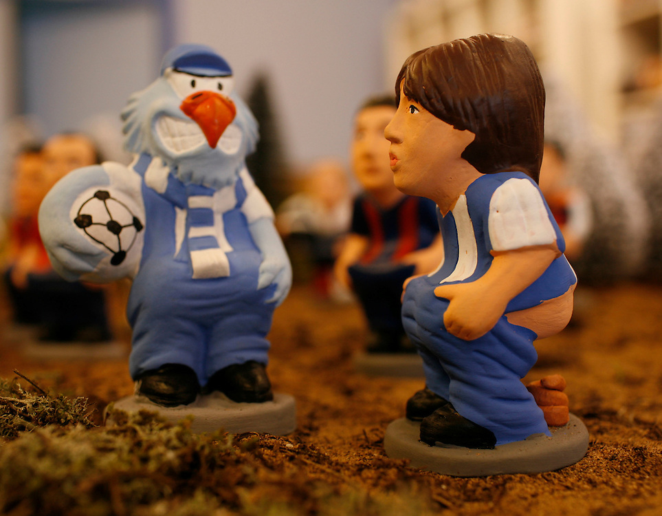 "Torroella de Mongri, Spain, 19 November 2009. .A company in Torroella de Montgrí (Girona, Spain) called ""caganer.com"" specialized in the production of ""caganers"" unveiled today  the new figures for Christmas as japanesse soccer player, Shunsuke Nakamura..A ""Caganer"" is a small figure from Catalonia, usually made of fired clay,  and depicted as squating person in the act defecating. .""Caganer"" is Catalan for pooper. It fomrs part of one of the typical figures of  the manger or ""Nativity"" scene together with Mary, .Joseph and the baby Jesus but hidden in a corner. It is a humorous figure, originally portraying a peasant wearing a .barretina (a red stocking hat), and seems to date from the 18th century when it  was believed that the figure's depositions  .would fertilize the earth to bring a properous year. With  the course of the time, the original  personage of this pooping figure .was  substituted with personalities from the political and sports world and other famous personalities."