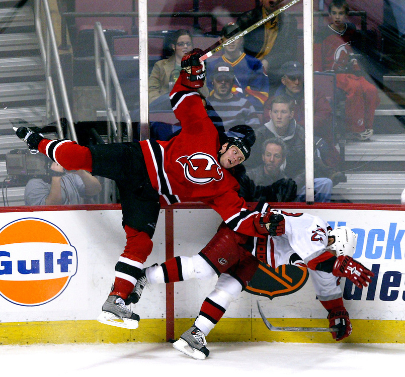 (SPORTS) East Rutherford 1/21/2003  The Devils Colin White becomes airborne as he lays a crushing hit on the Hurricanes #22 Sean Hill in the second period.   Michael J. Treola Staff Photographer....MJT
