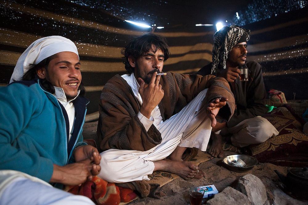Young Bedouin men relax in their remote home encampment in Wadi Rum, Jordan.