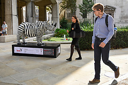 **CAPTION CORRECTION - Rhino statues are 750mm tall, not 750cm tall, as stated in previous captions**<br /> © Licensed to London News Pictures. 20/08/2018. LONDON, UK. Office workers view 'Freddie', a rhino painted by Glen Baxter, outside Guildhall.  At 750mm tall and weighing 300 kg, each rhino has been specially embellished by an internationally renowned artist.  21 rhinos are in place at a popular location in central London, forming the Tusk Rhino Trail, until World Rhino Day on 22 September to raise awareness of the severe threat of poaching to the species' survival.  They will then be auctioned by Christie's on 9 October to raise funds for the Tusk animal conservation charity.  Photo credit: Stephen Chung/LNP