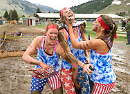 From left, Stephanie Roy, Sascha Estens and Charlotte Moats as team 'Merica, spread the love after crawling through a mud pit during the Ultimate Towner obstacle course race Sunday at Teton County Fairgrounds. See sports for a story and more photos from the 4-mile race around town.