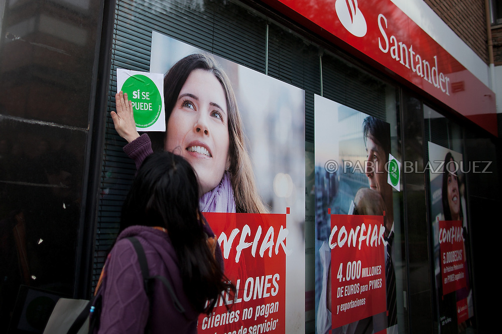 An anti eviction activist places a sticker reading 'Yes we can' at bank window after an 'escrache' outside the house of PP deputy Beatriz Rodriguez Salmones on April12, 2013 in Madrid, Spain. The Mortgage Holders Platform (PAH) and other anti evictions organizations have been organizing 'escraches' for several weeks under the slogan 'There are lives at risk' to claim the vote for a Popular Legislative Initiative (ILP) to stop evictions and facilitate social rent, outside Popular Party deputies' houses and offices. 'Escraches' are a form of peaceful protest that were used in Argentine in 1995 to publically denounce pardoned members of the dictatorship for their crimes at their doorsteps.