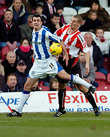 Photo: Leigh Quinnell.<br /> Brentford v Huddersfield Town. Coca Cola League 1. 21/01/2006. Huddersfields Danny Schofield clashes with Brentfords Andy Frampton.