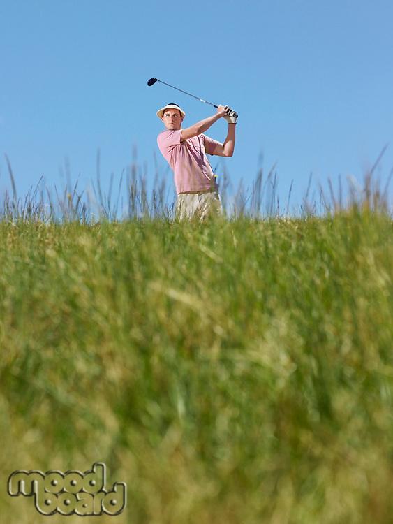 Male golfer driving ball