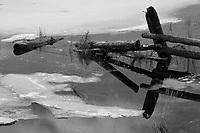 View of old fence terminating in partially frozen Lake LaRose Tead near Pasagshak Bay Road enroute to Pasagshak State Recreation Site, Kodiak, Alaska, Winter