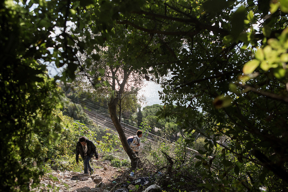 VENTIMIGLIA, ITALY - 20 NOVEMBER 2014: Eritrean refugees walk in a trail near the Italian-French border  in Ventimiglia, Italy, on November 20th 2014. They had first tried to cross the border by train in the morning, but were caught by the French police that pushed them back to the Italian border.<br /> <br /> The Ventimiglia-Menton border is the border between Italy and France crossed by migrants who decide to continue their journey up north towards countries such as Germany, Sweden, The Netherlands and the UK where the process to receive the refugee status or humanitarian protection is smoother and faster. in Ventimiglia, Italy, on November 17th 2014.