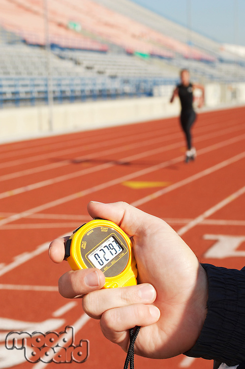 Man holding stopwatch close up of hand timing runner on running track