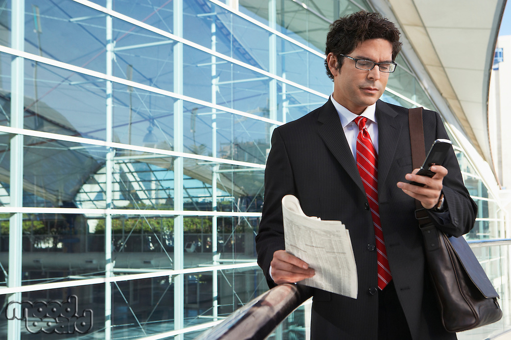 Businessman using mobile phone outside office building