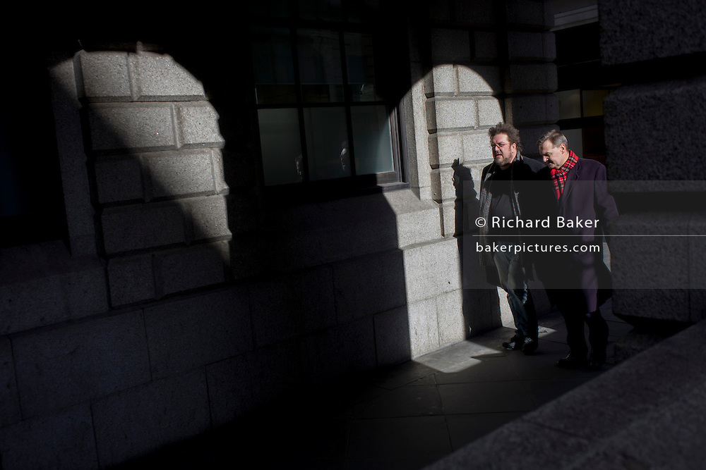 Two workers walk through sunlight under arches in a City of London street.