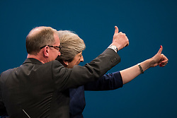 © Licensed to London News Pictures. 04/10/2017. Manchester, UK. British prime minister THERESA MAY and her husband PHILIP MAY wave to the crowd after delivering her leaders speech on the final day of the Conservative Party Conference. The four day event is expected to focus heavily on Brexit, with the British prime minister hoping to dampen rumours of a leadership challenge. Photo credit: Ben Cawthra/LNP