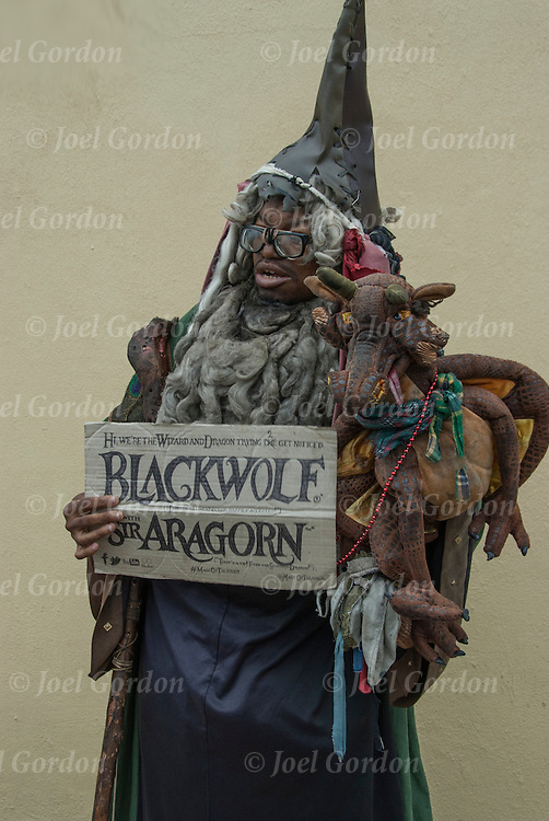 "Mermaid Parade marcher wearing  costume and holding sign "" Blackwolf and Air Aragorn"" before the start of the parade in Coney Island."