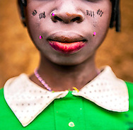 Umou, 16, puts on her best clothes and lipstick for a baby naming ceremony in a small village in the Kalal&eacute; District of Benin. She is one of the few girls who goes to school past a young age. <br />