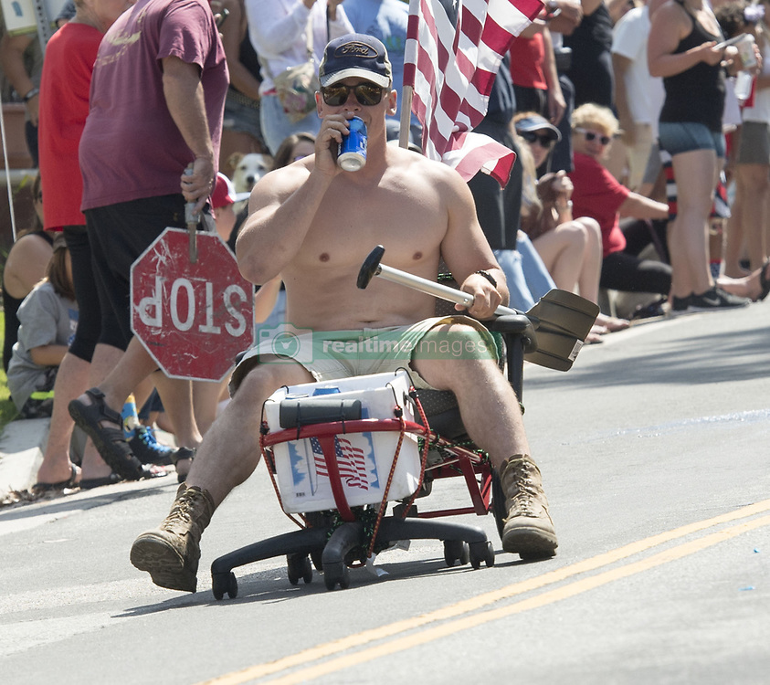 July 4, 2017 - San Clemente, California, U.S - San Clemente residents cobbled together anything with wheels for the Annual July 4th Chair Races along Avenida Rosa in celebration of American Independence Day on Tuesday.  The Annual event brings out anyone with a an office chair inspired non motorized vehicle they roll down the normally quiet street of Avenida Rosa each year.  All ages participated this year with over a thousand people coming out to watch.  Racers are obligated to push or pull their handmade contraptions up the hill to start again.  Several water fight ambushes cool off the racers as they try their luck on making it to the finish line.  A young man drinks a beer from an onboard cooler on Tuesday. (Credit Image: © David Bro via ZUMA Wire)