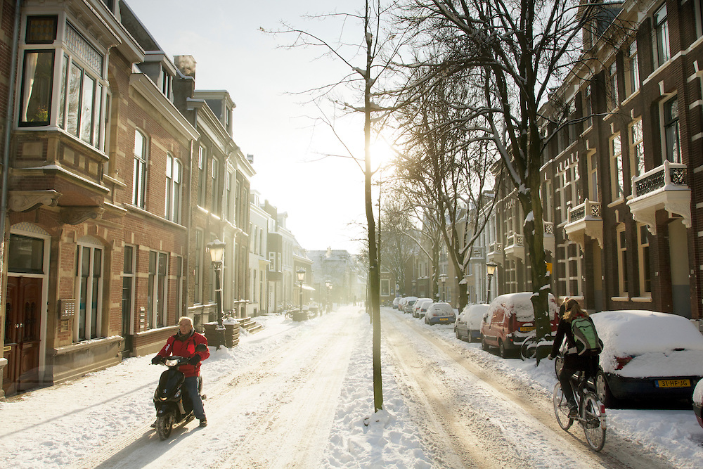 Een man op een brommer en een fietser proberen voorzichtig vooruit te komen over het gladde wegdek in de Predikherenkerkhof in Utrecht.<br /> <br /> A man on a moped and a cyclist are riding on a slippery road at the Predikherenkerkhof in Utrecht.