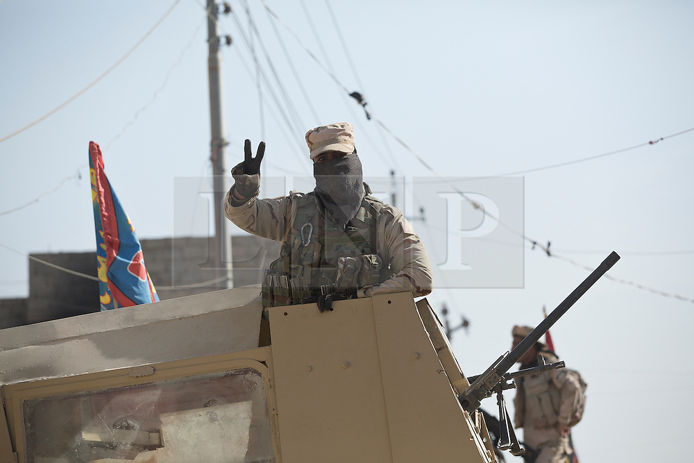 Licensed to London News Pictures. 11/11/2016. Mosul, Iraq. A soldier, belonging to the Iraqi Army's 9th Armoured Division, flashes a victory sign from the turret of an armoured Humvee as his unit visits Mosul's Al Inisar district on the south east of the city. The Al Intisar district was taken four days ago by Iraqi Security Forces (ISF) and, despite its proximity to ongoing fighting between ISF and ISIS militants, many residents still live in the settlement without regular power and water and with dwindling food supplies.<br /> <br /> The battle to retake Mosul, which fell June 2014, started on the 16th of October 2016 with Iraqi Security Forces eventually reaching the city on the 1st of November. Since then elements of the Iraq Army and Police have succeeded in pushing into the city and retaking several neighbourhoods allowing civilians living there to be evacuated - though many more remain trapped within Mosul.  Photo credit: Matt Cetti-Roberts/LNP