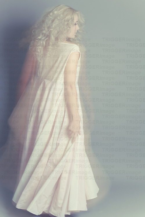 Young blonde female wearing long white dress