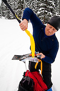 Backcountry skier, Dale Embleton, cuts smoked salmon with his shovel since he can't find a knife. Being prepared for all conditions and circumstances is necessary to survive during wiinter in Colorado.