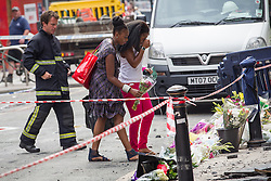 © Licensed to London News Pictures . FILE PICTURE DATED 15/07/2013 . Oldham Street , Manchester , UK . Two women place flowers at the scene , in front of Paul's Hair World . The scene on Oldham Street following a fire at Paul 's Hair World on 13th July which claimed the life of fireman Stephen Hunt . Photo credit : Joel Goodman/LNP