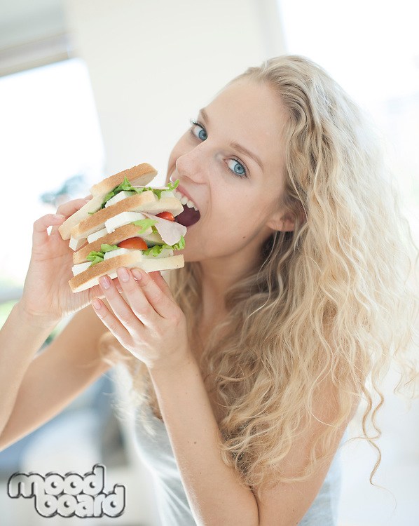 Portrait of impatient woman eating large sandwich in house