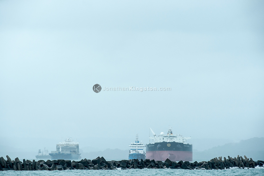 Large ships behind a breakwater near the mouth of the Panama Canal.