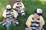 "24 MARCH 2004 - PHOENIX, AZ, USA: Members of the Maricopa County Jail's Juvenile Chain Gang eat their lunches at a worksite in Phoenix, AZ, March 24, 2004. The juveniles volunteer to serve Maricpoa County Sheriff Joe Arpaio's chain gang. The sheriff, who claims to be ""the toughest sheriff in America,"" has chain gangs in both the men's and women's jails and now has a chain gang for juveniles sentenced and serving time as adults in the county jail system. The sheriff claims it is the only juvenile chain gang in the country.   PHOTO BY JACK KURTZ"