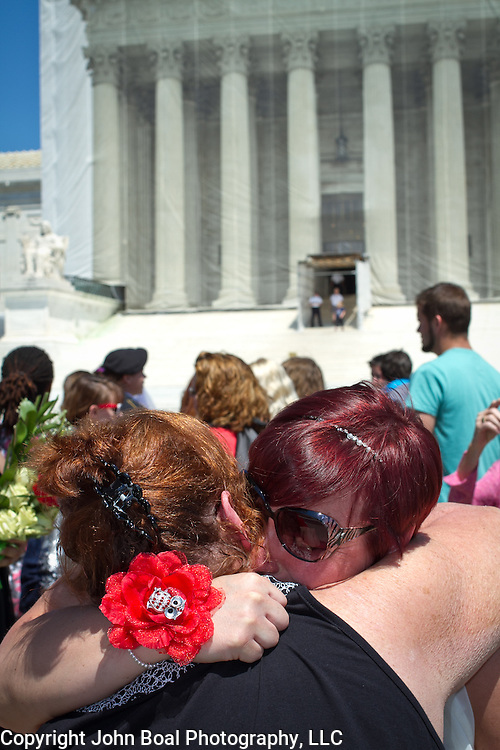 Shannon Glatz, of Akron Ohio, embraces her soon to be mother in-law, Penny Pillo, in front of the Supreme Court of the United States, on June 21, 2013.  Twenty-five gay couples traveled to Washington on the C-Bus of Love to get married en masse the week before decisions are expected to be made on the Defense of Marriage Act (DOMA) and Proposition 8.  John Boal photography