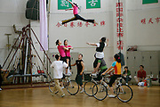A troupe tries out its cycling act at the Shanghai Circus World, Shanghai, China, where acrobat Xiaoli Cao practices. (From the book What I Eat: Around the World in 80 Diets.)