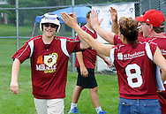 Shawn Fitzgerald (right) is congratulated by teammates after scoring a run during the Miracle League Festival, a softball tournament for players with intellectual and physical challenges at George School Saturday June 20, 2015 in Newtown, Pennsylvania. (Photo by William Thomas Cain)