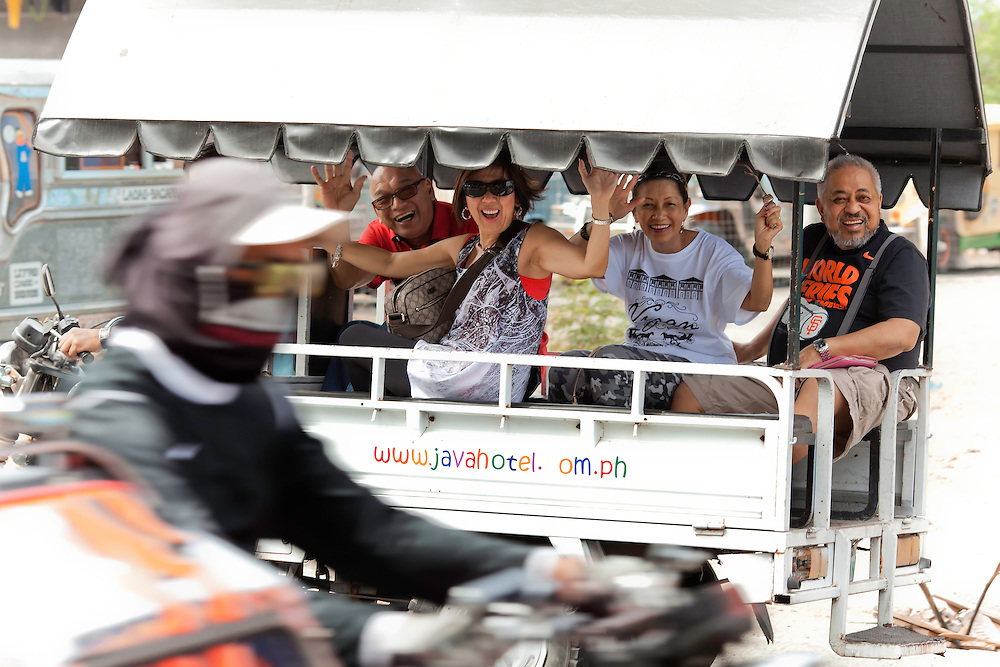 Happy riders head into town on hotel shuttle, in Laoag, Philippines. Copyright 2015 Reid McNally.
