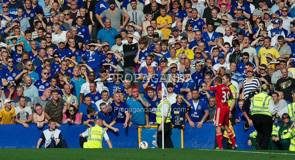 LIVERPOOL, ENGLAND - Saturday, October 1, 2011: Liverpool's Craig Bellamy sheilds himself from bottles thrown at him from the stands by Everton supporters during the Premiership match at Goodison Park. (Pic by David Rawcliffe/Propaganda)