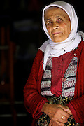 A old lady looks out of her doorway in a village in Turkey.