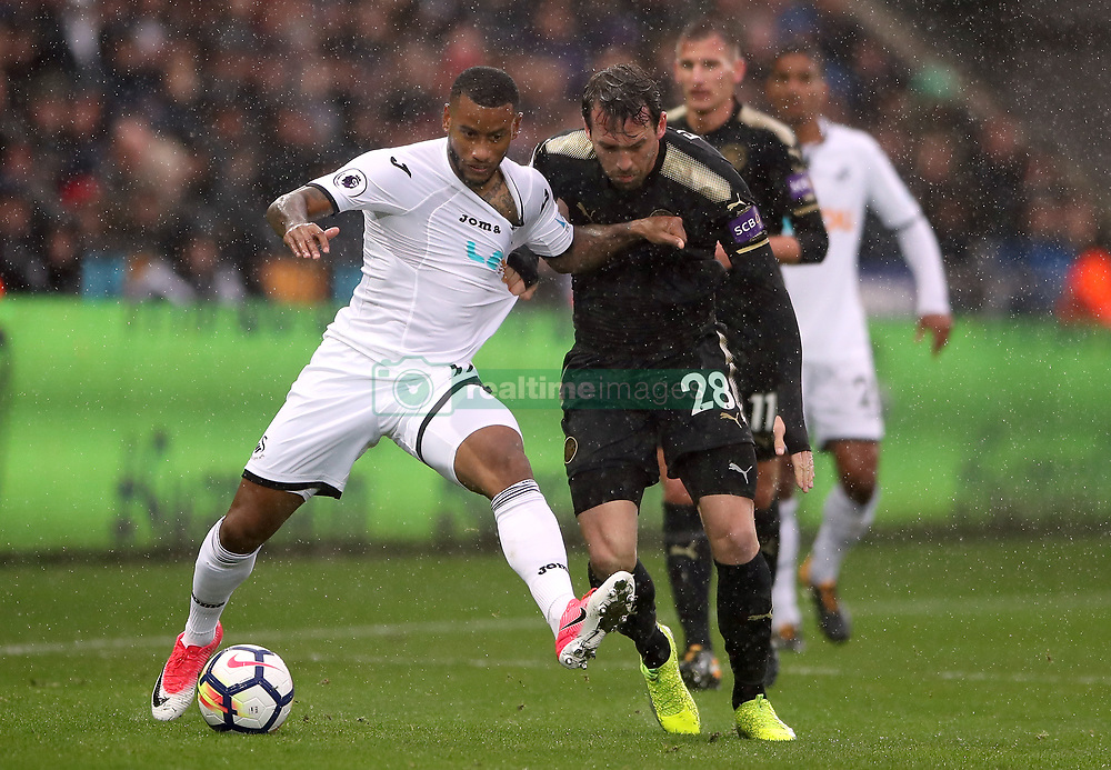 Leicester City's Christian Fuchs (right) and Swansea City's Luciano Narsingh battle for the ball during the Premier League match at the Liberty Stadium, Swansea.