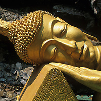 Asia, Laos, Luang Prabang, Statue of Reclining Buddha at shrine near Wat Tham Phu Si Buddhist temple