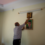 August 12, 2012 - Kafa Safra, Efrin, Syria: Mustapha, a Syrian Kurdish from Kafra Safra village, hangs the picture of his dead son Rudi, a Kurdistan Workers' Party (PKK) fighter killed during combat in the Turkish mountains...PKK has been fighting an armed struggle against the Turkish state for an autonomous Kurdistan and greater cultural and political rights for the Kurds in Turkey, Iraq, Syria and Iran. Founded on 27 November 1978 in the village of Fis, was led by Abdullah Öcalan. The PKK's ideology was originally a fusion of revolutionary socialism and Kurdish nationalism - although since his imprisonment, Öcalan has abandoned orthodox Marxism. The PKK is listed as a terrorist organization by Turkey, the United States, the European Union and NATO. (Paulo Nunes dos Santos)
