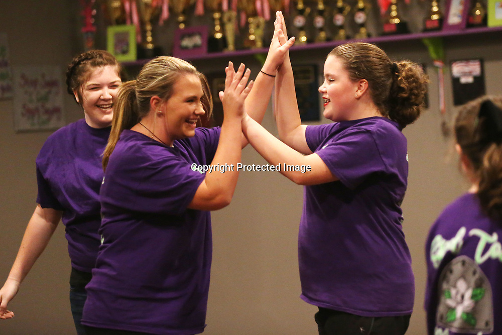 Cloggers Jennifer Vance, 18, left, and Megan Leech, 13, high-five after nailing their clogging routine in practice at the Steel Toe Magnolias studio in Amory.