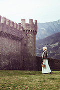 a woman in a white period dress is walking along a castle