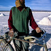 P&aacute;nfilo  Marques  that lives in population of Colchani internal every day through several km in the salar for fourteen years to be going to be employed at the extracion of of salt.  Salar de Uyuni ( Uyuni salt flat ) . Department  of Potos&iacute;  ( Los Lipez).  South West  Bolivia. <br /> Adult Altiplano America Andes Arid  Aridity Barren  Bicycle Bolivia Color Colour Cone  Day Daytime  Department  Desert Desolate Desolation Dry  Exterior Extraction  Geography Hard Heat Highlands  Horizon Human  Latin America Lake  Los Lipez Male Man Men Miner Mining Nature  Resource  Natural  One Outdoors Outside  Pan People  Person Pyramide Potos&iacute;  Production  Region Resource Rural Salar de Uyuni  Salt Flat  Salt Pan  Salt lake  Scenic Seasoning  Single Shape South America  Southwest  Sud Sunglasses  Surface Travel Vertical West White Work  Worker Working