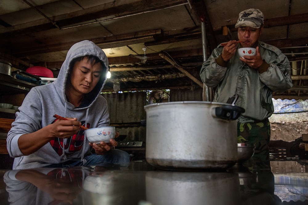 Sand dredgers stop for lunch in the town of Simaogangzhen, Yunan China. The dredged sand is sold locally and to large scale construction sites in nearby major cities such as Kunming and Jinhong.