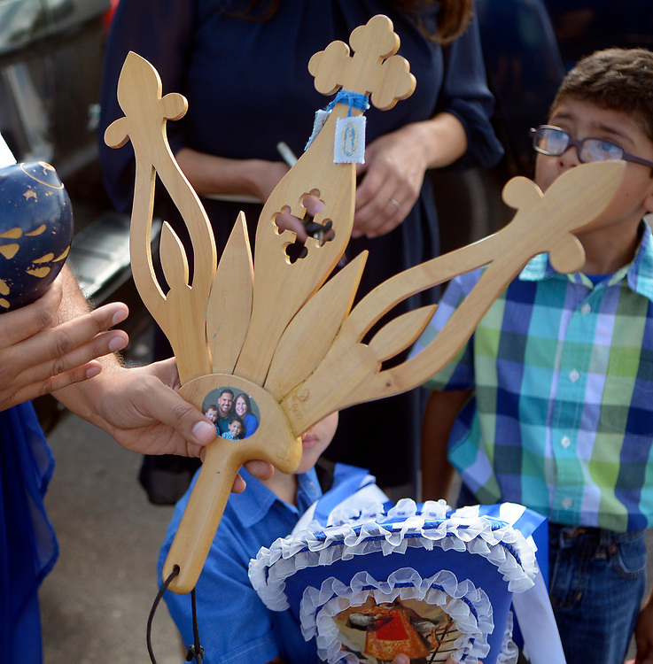 gbs081017f/RIO-WEST -- Tim Lucero holds his palma with a photo of his family that he carries in the Las Fiestas de San Lorenzo Procession on Thursday, August 10, 2017.(Greg Sorber/Albuquerque Journal)