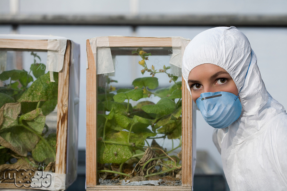 Worker in protective mask and suit by plants portrait