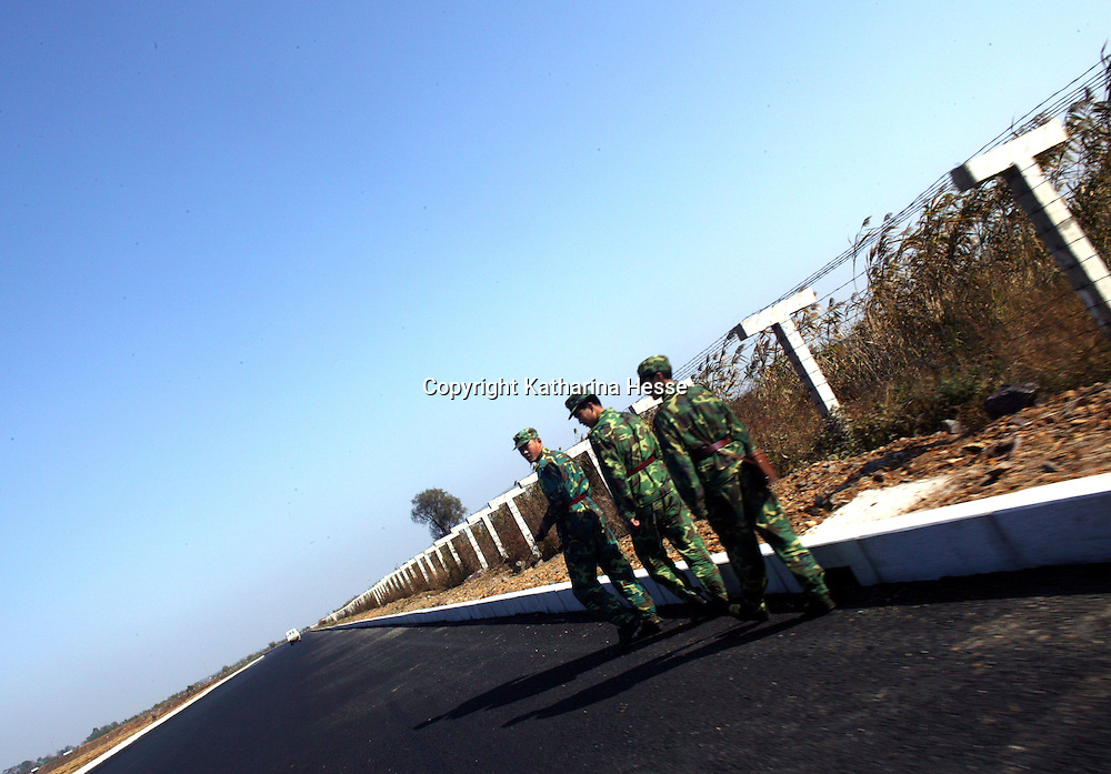 NORTHERN CHINA , OCTOBER-26: border guards walk along the newly built fence at the North Korean in China , October 26,2006. In some parts, the border is a small creek where people from both sides meet unofficially. As a result of the nuclear test by North Korea in early October, the border is surveilled more strictly and according to locals, meetings have become sensitive.