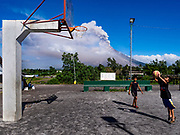 23 JANUARY 2018 - DARAGA, ALBAY, PHILIPPINES: Children play basketball on a recreation yard in Daraga while the Mayon volcano erupts Tuesday. The Mayon volcano continued to erupt Tuesday, although it was not as active as it was Monday. There were ash falls in communities near the volcano. This is the most active the volcano has been since 2009. Schools in the vicinity of the volcano have been closed and people living in areas affected by ash falls are encouraged to stay indoors, wear a mask and not participate in strenuous activities.    PHOTO BY JACK KURTZ