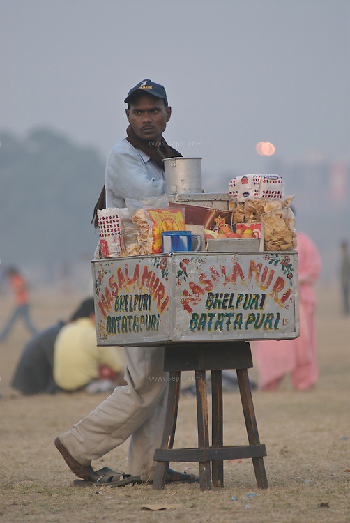 A hawker selling Masala Muri and Bhel Puri as evening falls on the maiden near victoria memorial, Kolkata, January 2007
