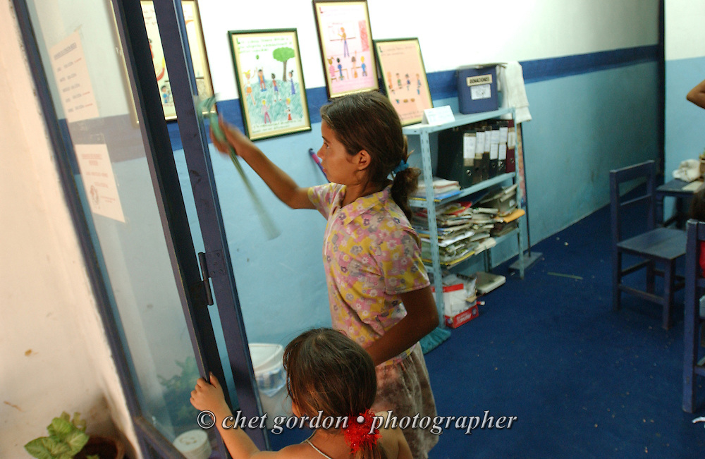 ASUNCION, PARAGUAY.  Two young Paraguayan street girls practice using a squeegee on a glass door in the Asociacion Cultural Justicia y Verdad (Association of Cultural Justice and Truth) in Asuncion, Paraguay on Friday evening, March 17, 2006. The shelter founded by Dr. Chantal Hulin, is run out of a renovated auto garage, where volunteers provide showers, administer health care, simple meals, and classroom activities to some of the hundreds of homeless street children that panhandle and clean windshields for money on the neighborhood streets.
