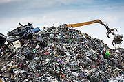 Grab machine organising metal recycling of scrap metal, cars and autos to avoid environmental pollution, England