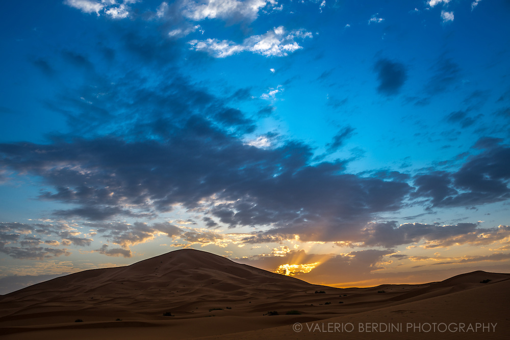 Sun rises beyond the scattered clouds and over sand dunes in the Sahara in Merzouga. Morocco