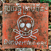Danger Land Mines Sign with Skull and Crossbones at Koh Ker Temples, Cambodia<br /> The Koh Ker temples in Cambodia offer a fascinating view of pyramids, sanctuaries, palaces, moats and tombs built by Jayavarman IV, ruler of the Khmer Empire in the 10th century.  But as peaceful and secluded as these ruins are, signs warn of dangers buried in the surrounding jungle.  When Pol Pot, the ruthless dictator of the Khmer Rouge, was overthrown in Phnom Penh in 1979, his army planted land mines which he called &ldquo;the perfect solders&rdquo; because they were always ready to explode.  Approximately three million have been cleared, but up to six million remain. They still kill hundreds a year, usually boys, and have caused 40,000 amputees. So, don&rsquo;t wander off the beaten path &hellip; literally.