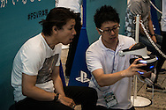 """A visitor receives explanations by a staff member for using  the Sony PlayStation VR headset during a preview at the exhibition """"Odaiba Dream Experience presented by PlayStation VR'' at the Fuji Television Headquarters Building, in Tokyo. 26/07/2016-Tokyo, JAPAN"""