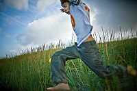 Boy running through tall grass playing football.